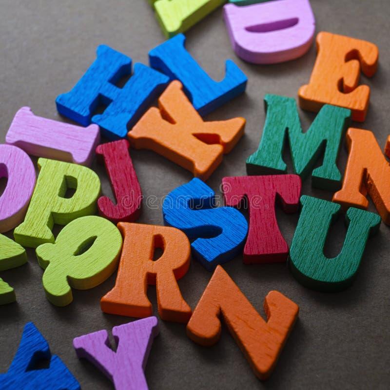 Lettres en bois colorées sur fond de bois photos libres de droits
