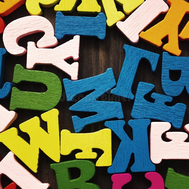 Lettres en bois colorées sur fond de bois image libre de droits