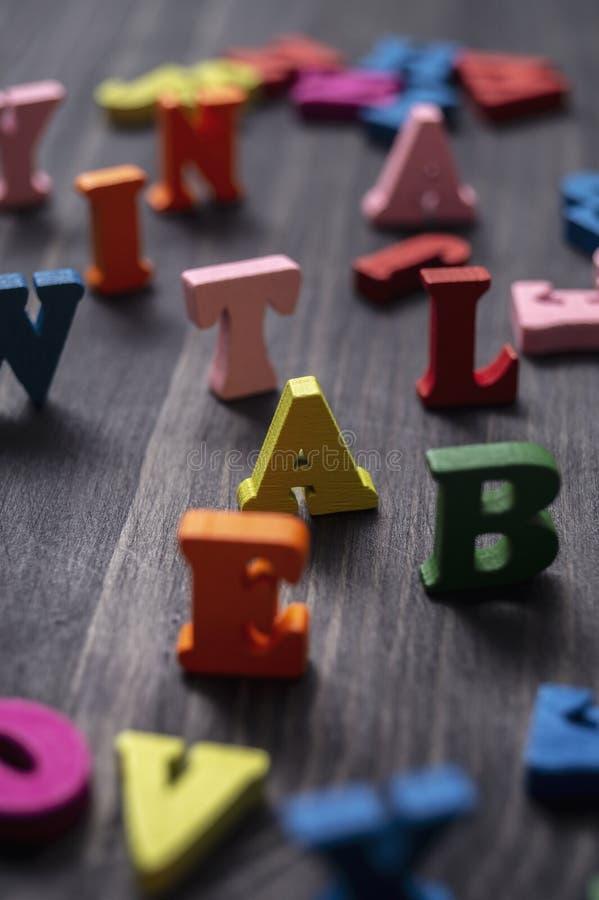 Lettres en bois colorées sur fond de bois images libres de droits