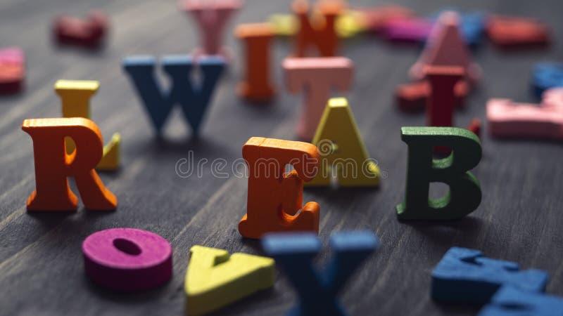 Lettres en bois colorées sur fond de bois photos stock