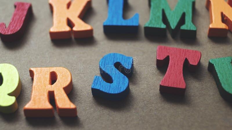 Lettres en bois colorées sur fond de bois image stock