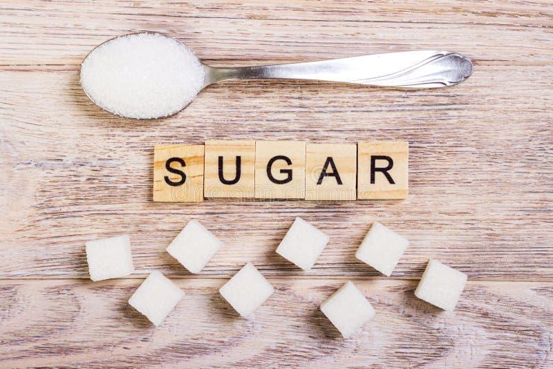 Lettres en bois de bloc de diabète avec la pile de sucre raffiné et de sucre sur une cuillère image libre de droits