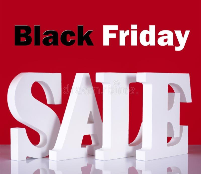 Lettres en bois de vente de Black Friday sur le fond rouge photo stock