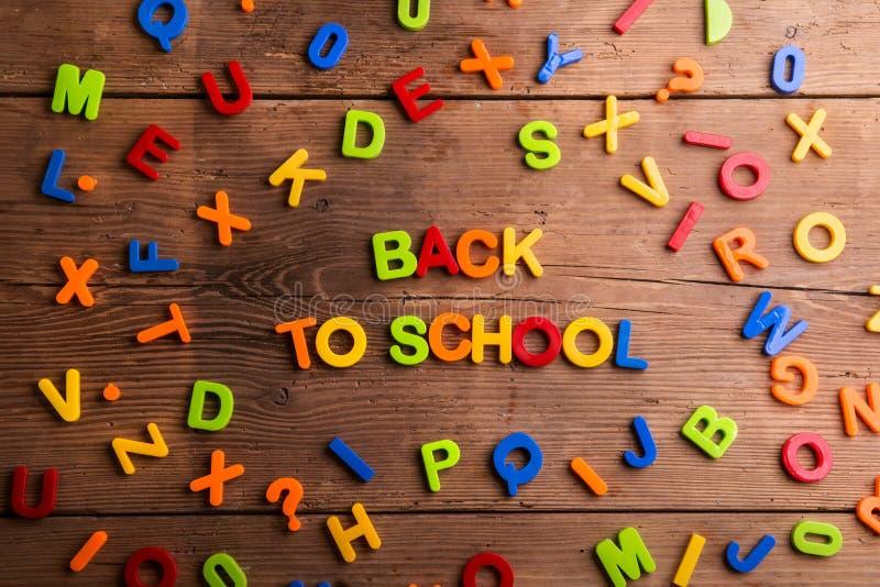 Lettres en plastique colorées, nombres, de nouveau à l'école, backg en bois photographie stock