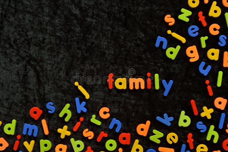Lettres magnétiques sur le noir avec le mot FAMILLE photographie stock libre de droits