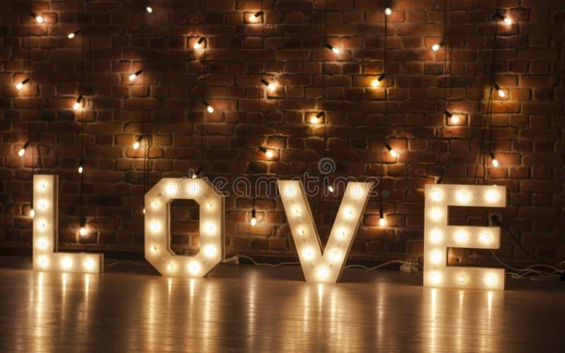 Lettres rougeoyantes de l'amour contre un contexte des lumières et des murs de briques photos libres de droits