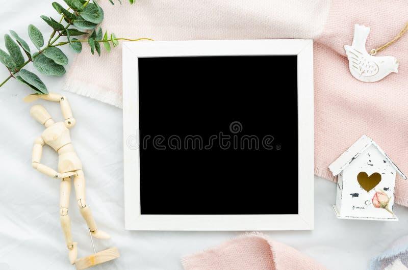 Lettreting imita encima del marco blanco de la foto de la frontera de la plantilla con el fondo negro, la mini casa y el maniquí  fotografía de archivo libre de regalías