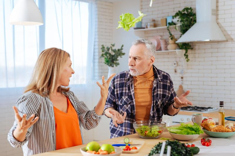 Wife throwing lettuce into air having argument with husband. Lettuce into air. Crazy angry wife throwing lettuce into air while having argument with husband royalty free stock images