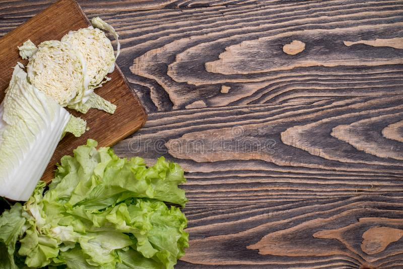 Lettuce, cabbage, sweet red pepper on a wooden background. Vegetarian vegetables for cooking salad. Diet and healthy nutrition. Fresh green Lettuce, cabbage royalty free stock photos