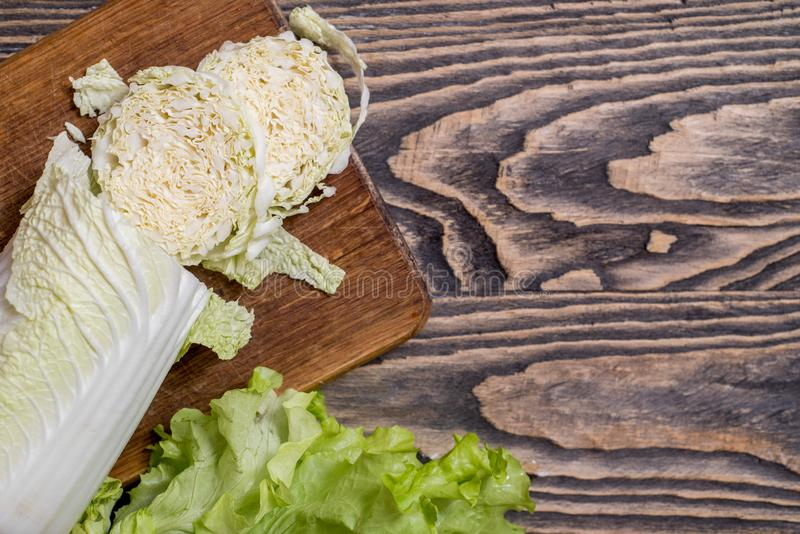 Lettuce, cabbage, sweet red pepper on a wooden background. Vegetarian vegetables for cooking salad. Diet and healthy nutrition. Fresh green Lettuce, cabbage stock photo