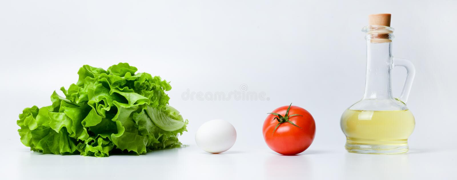 Lettuce, egg, tomato and vegetable oil in a glass container. Horizontal composition with individual products. stock image