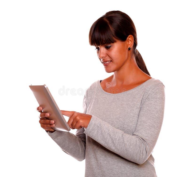 Lettura affascinante della giovane donna sullo schermo del pc della compressa immagini stock libere da diritti