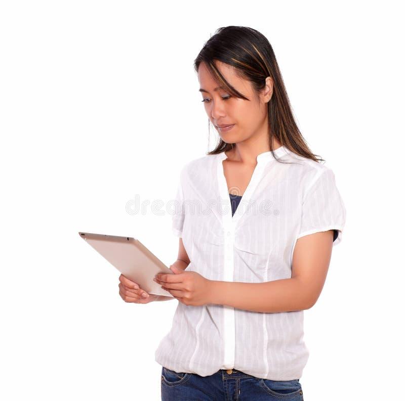 Lettura affascinante della giovane donna sullo schermo del pc della compressa immagini stock