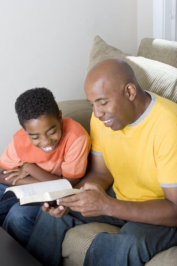Lettura afroamericana dell'uomo con suo figlio immagini stock libere da diritti