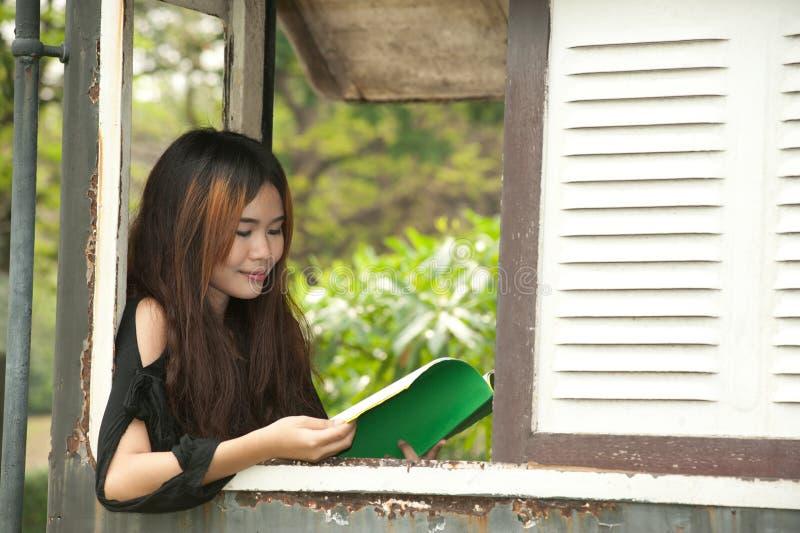 Lettura asiatica della donna alla finestra di vecchia stanza del treno. immagini stock libere da diritti