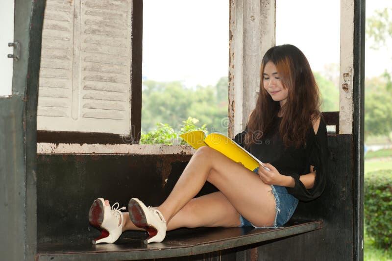 Lettura asiatica della donna nella vecchia stanza del treno. fotografia stock libera da diritti
