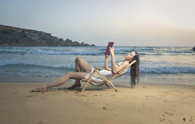 Lettura del libro alla spiaggia immagine stock libera da diritti