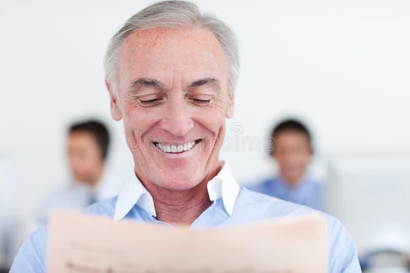 Lettura del Senior Manager al suo scrittorio fotografia stock