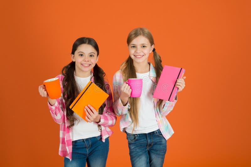 Lettura dell'attività piacevole Bambini delle ragazze con il fondo arancio delle tazze del tè e dei libri Gli amici spendono i li fotografia stock libera da diritti