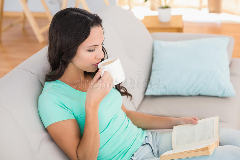 Lettura della donna e caffè bevente sullo strato fotografia stock