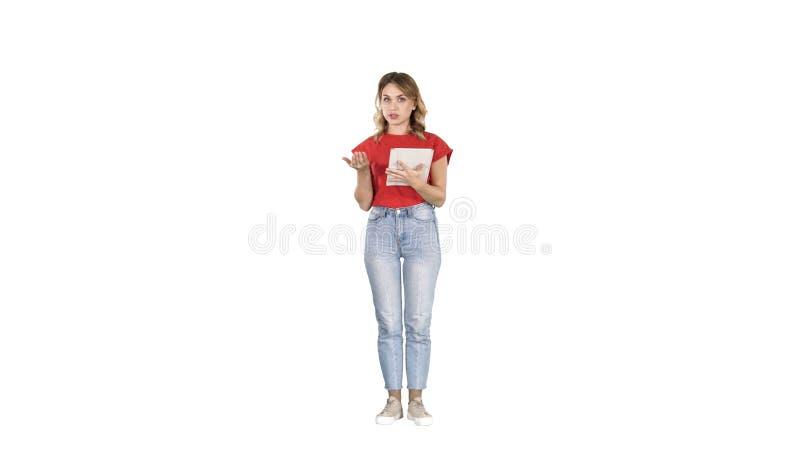 Lettura della donna sulla compressa e parlare con macchina fotografica su fondo bianco fotografia stock libera da diritti