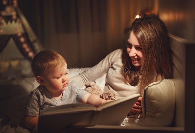 Lettura della famiglia di sera le madri legge i bambini libro prima di goin immagine stock
