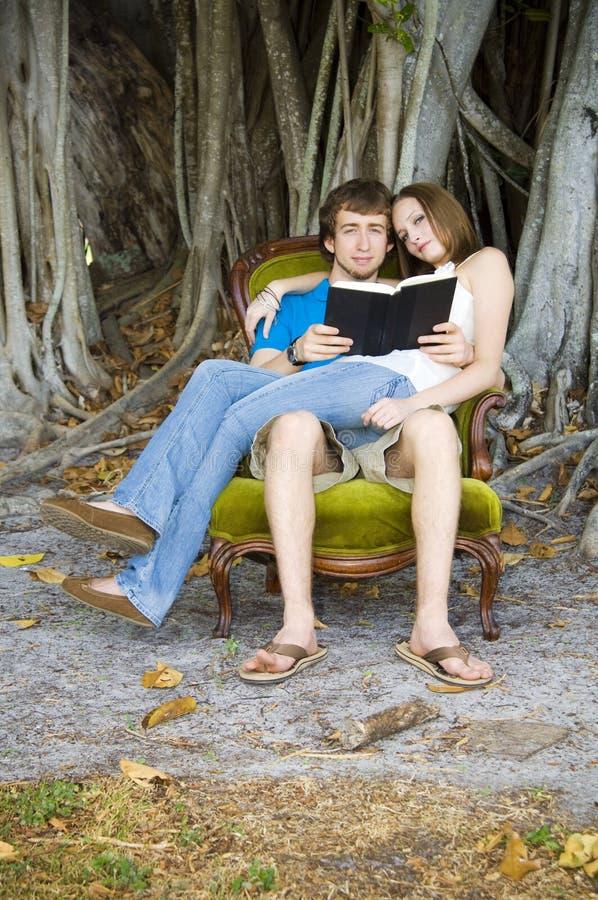 Lettura delle coppie sotto l'albero fotografie stock