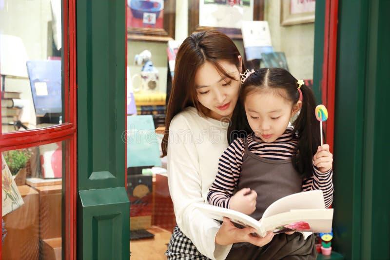 Lettura di pratica della bambina nel mercato brillantemente illuminato immagine stock