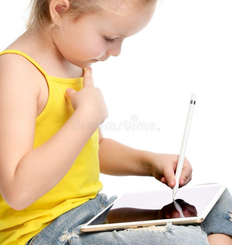 Lettura di seduta del bambino della ragazza che impara attingendo il cuscinetto digitale del touch screen della compressa con la  fotografia stock libera da diritti