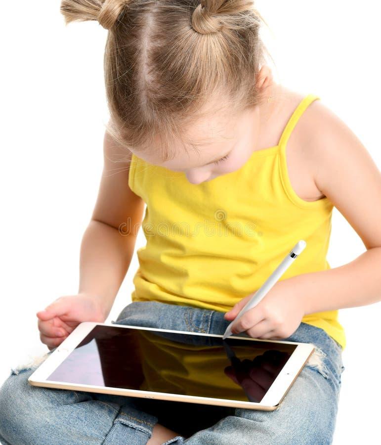 Lettura di seduta del bambino della ragazza che impara attingendo il cuscinetto digitale del touch screen della compressa con la  immagine stock