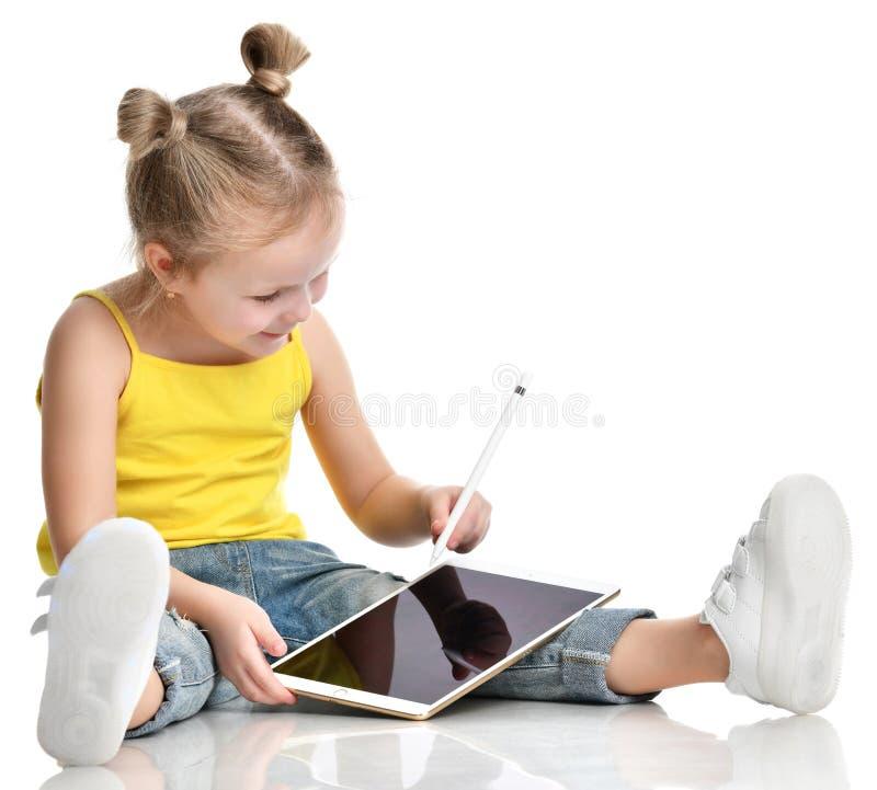 Lettura di seduta del bambino della ragazza che impara attingendo il cuscinetto digitale del touch screen della compressa con la  fotografia stock
