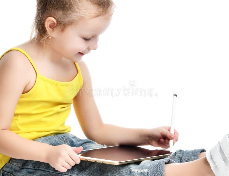 Lettura di seduta del bambino della ragazza che impara attingendo il cuscinetto digitale del touch screen della compressa con la  immagine stock libera da diritti