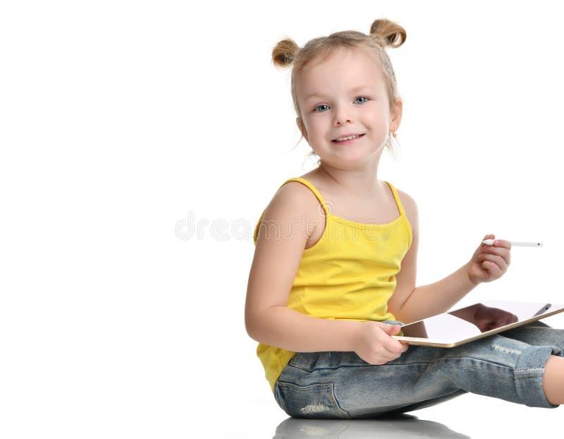 Lettura di seduta del bambino della ragazza che impara attingendo il cuscinetto digitale del touch screen della compressa con la  immagini stock libere da diritti