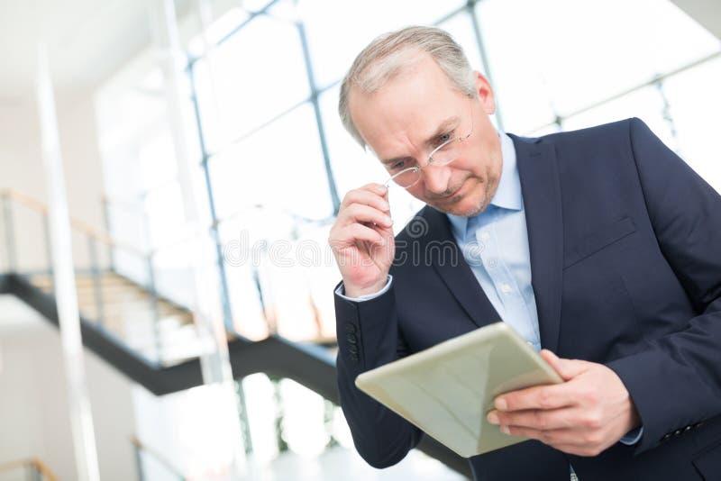 Lettura di Wearing Eyeglasses While dell'uomo d'affari sulla compressa di Digital immagini stock