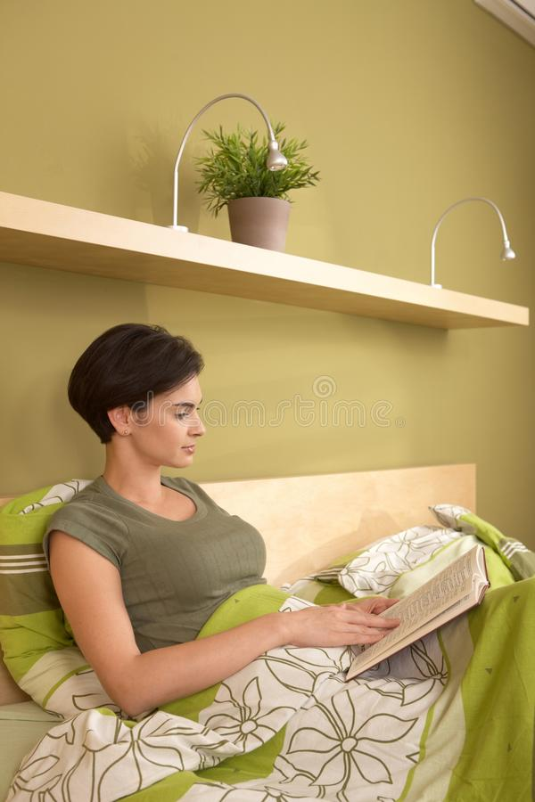lettura graziosa della donna dell'Metà di-adulto nella camera da letto fotografia stock libera da diritti