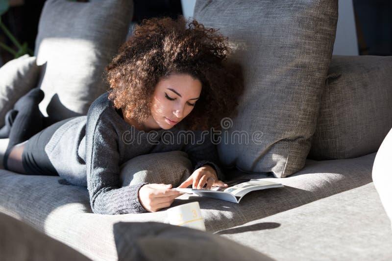 Lettura ricca della ragazza qualcosa sul suo sofà immagini stock libere da diritti