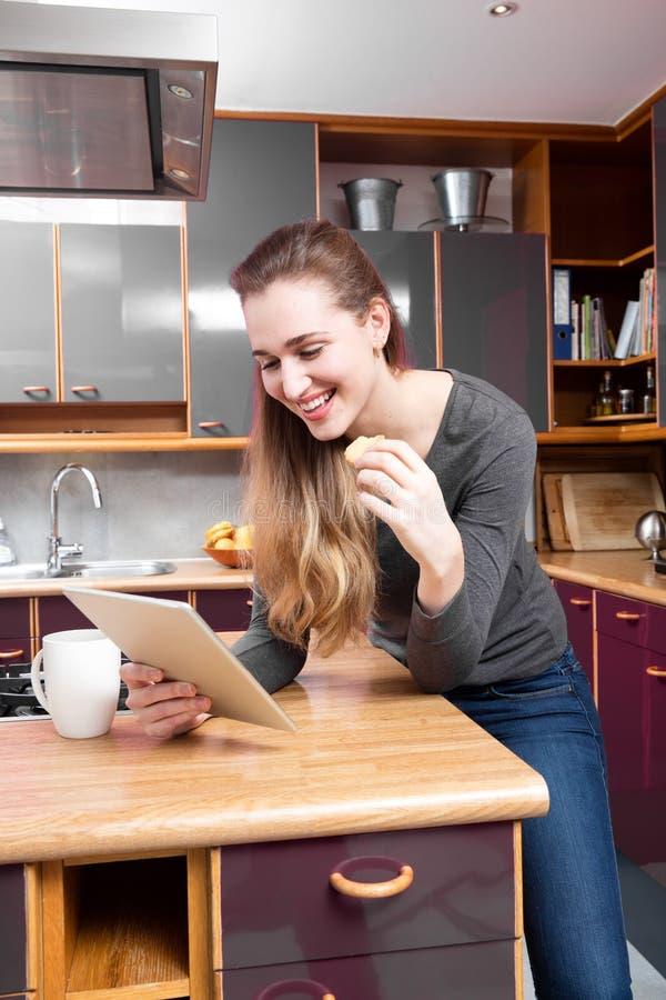 Lettura splendida sorridente della giovane donna sulla tecnologia domestica di rilassamento fotografia stock libera da diritti