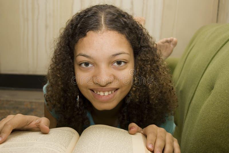 Lettura teenager del giovane afroamericano immagini stock libere da diritti