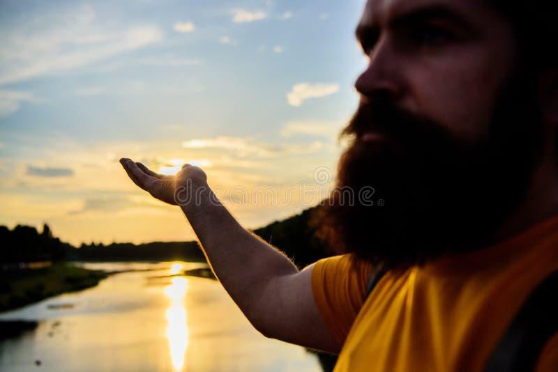 Letzter Sonnenstrahl des Fanges Die männliche Hand, die auf Sonne im blauen Himmel auf Abendzeit zeigt, bewundern Landschaft Zu b lizenzfreie stockbilder