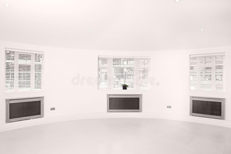 Leuchte-, heller und luftigerraum mit drei Windows stockbild