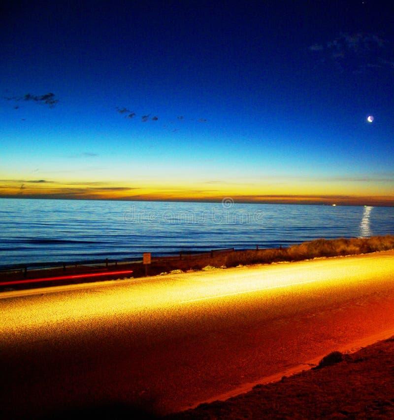 Leuchte, Nacht, Ozean u. Mond stockfotografie