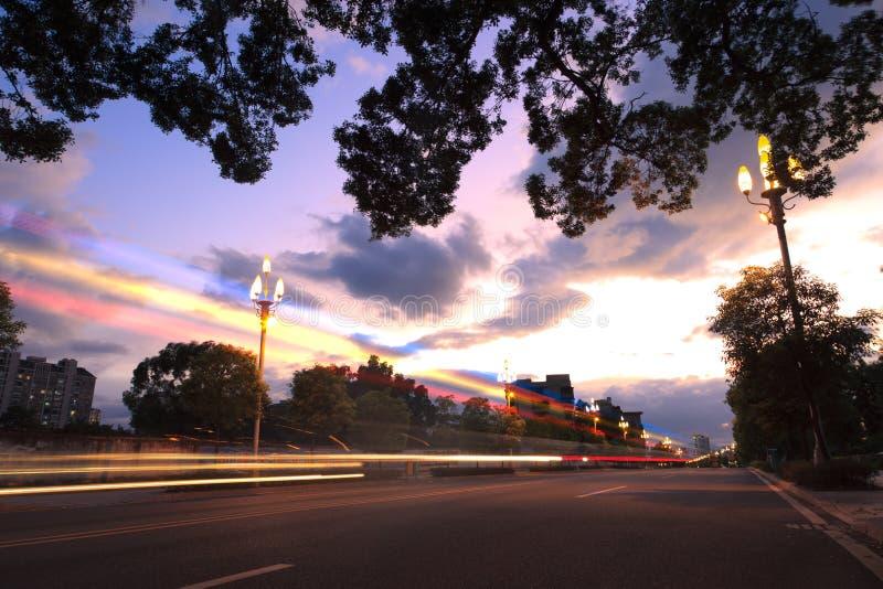 Leuchte schleppt auf der städtischen Straße an der Dämmerung stockfotos