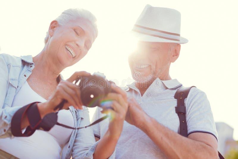 Leuchtende ältere Paare, die Fotos auf Kamera betrachten lizenzfreie stockbilder