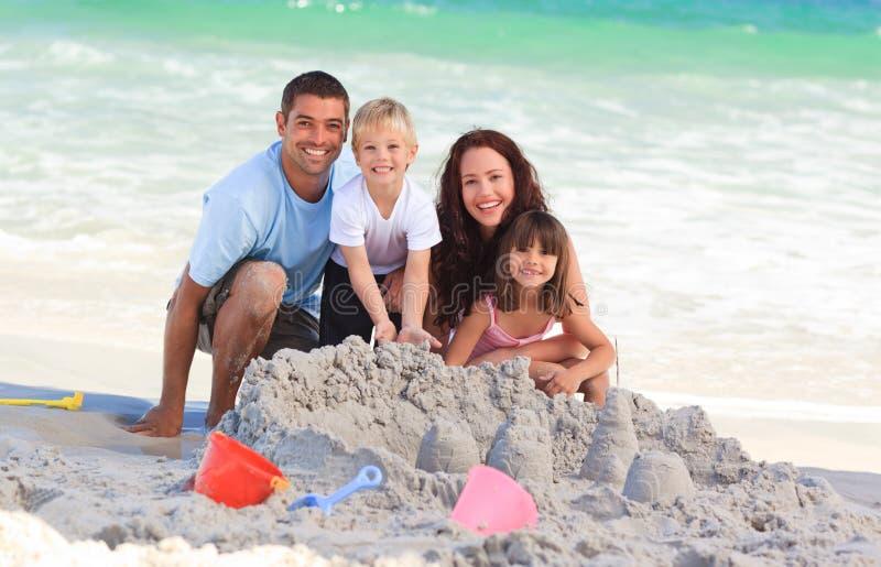 Leuchtende Familie am Strand lizenzfreie stockfotografie