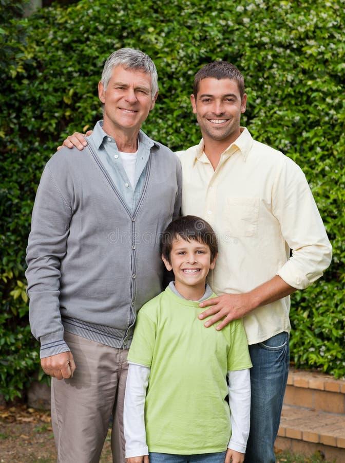 Leuchtende Familie, welche die Kamera im Garten betrachtet stockfotos