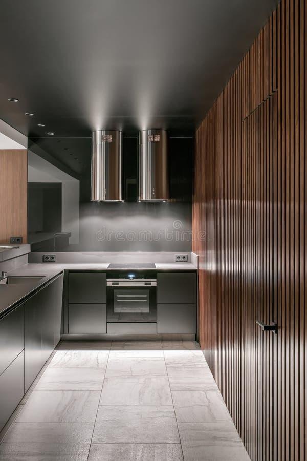 Leuchtende moderne Küche mit glatten metallischen Oberflächen stockbilder