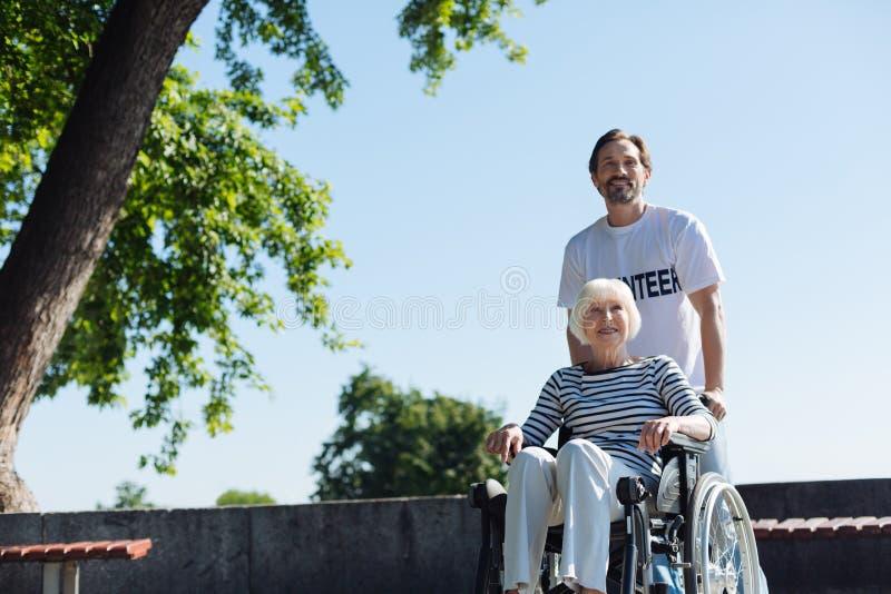 Leuchtender angenehmer Mann, der ältere Dame heraus im Park nimmt stockbild