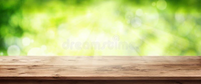 Leuchtender grüner Frühlingshintergrund mit Holztisch lizenzfreies stockfoto