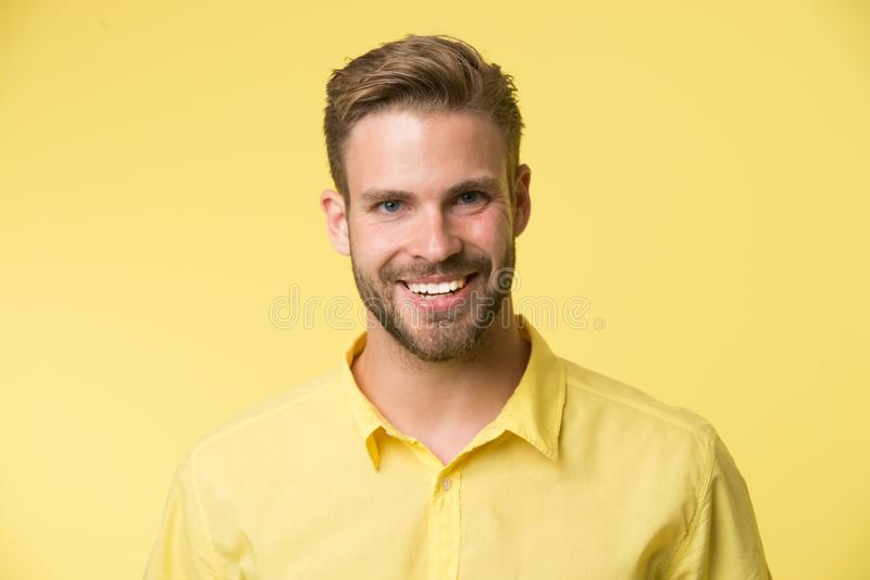 Leuchtendes Lächeln Lächelndes Gesicht des Mannes, das sicher gelben Hintergrund aufwirft Mannshopberater schaut nettes überzeugt stockfotos