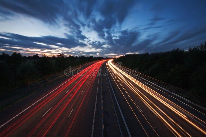 Leuchtespuren auf einer Autobahn an der Dämmerung stockbild